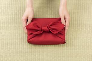 風呂敷包の手土産を渡す女性の手の写真素材 [FYI04811872]