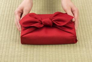 風呂敷包の手土産を渡す女性の手の写真素材 [FYI04811874]