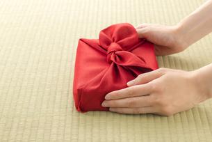風呂敷包の手土産を渡す女性の手の写真素材 [FYI04811876]