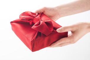 風呂敷包の手土産を渡す女性の手の写真素材 [FYI04811880]