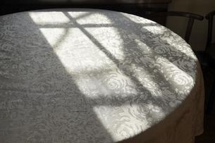 陽の射すレース生地のかかったテーブルの写真素材 [FYI04812205]
