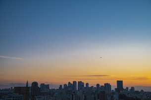 夕暮れの新宿方面の高層ビル群と飛行するジェット機の写真素材 [FYI04812451]