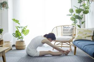部屋でストレッチをする若い女性の写真素材 [FYI04812664]