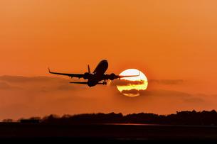 美しい夕焼け空を背景に航空機が飛行する光景の写真素材 [FYI04812998]
