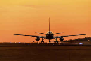 最高に美しい夕焼け空を背景に飛行機が飛び立つ風景の写真素材 [FYI04813013]