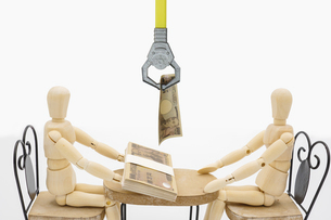 取引するデッサン人形からマジックハンドで消費税を徴収するイメージの写真素材 [FYI04814268]