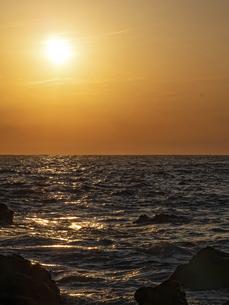 夕暮れ時の太陽と波に反射する光の写真素材 [FYI04814347]