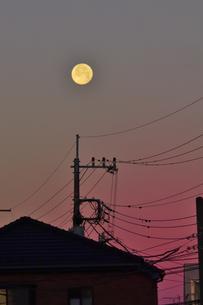 朝焼けに浮かぶ大きな月と建物と電線の写真素材 [FYI04814413]