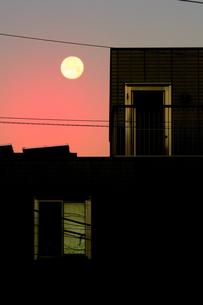 朝焼けに浮かぶ大きな月と建物の写真素材 [FYI04814418]