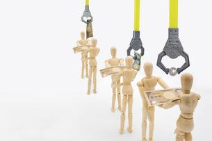 取引するデッサン人形からマジックハンドで消費税を徴収するイメージの写真素材 [FYI04815003]