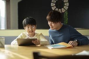 タブレットで学習する男の子と家庭教師の写真素材 [FYI04815892]