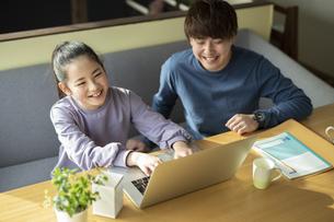 パソコンで学習する女の子と家庭教師の写真素材 [FYI04815898]