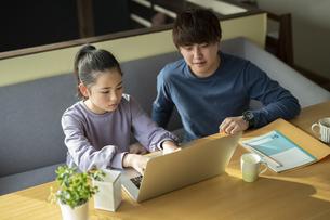 パソコンで学習する女の子と家庭教師の写真素材 [FYI04815899]