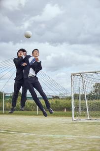 河川敷でボールを競り合うサラリーマンの写真素材 [FYI04816521]