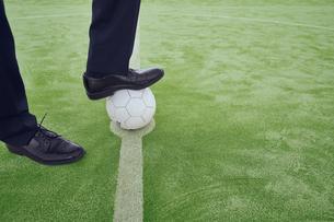 サッカーボールを足で押さえるサラリーマンの足元の写真素材 [FYI04816530]