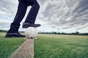 サッカーボールを足で押さえるサラリーマンの足元の写真素材 [FYI04816531]