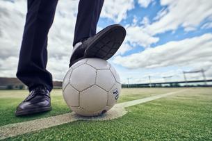 サッカーボールを足で押さえるサラリーマンの足元の写真素材 [FYI04816532]