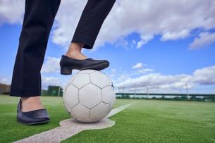 サッカーボールを足で押さえるOLの足元の写真素材 [FYI04816545]