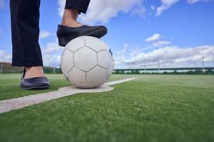 サッカーボールを足で押さえるOLの足元の写真素材 [FYI04816546]