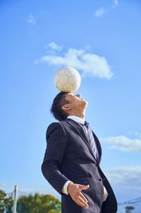 額の上にボールを乗せてバランスを取るサラリーマンの写真素材 [FYI04816549]