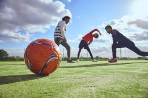 ボール越しのストレッチを行う3人のスポーツマンの写真素材 [FYI04816552]