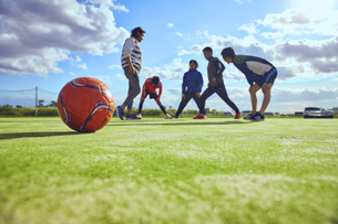 ボール越しのストレッチを行う5人のスポーツマンの写真素材 [FYI04816553]