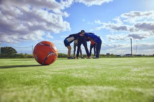 ボール越しの円陣を組む5人のスポーツマンの写真素材 [FYI04816554]