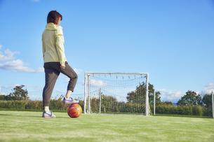 サッカーボールを足で押さえる女子サッカープレイヤーの写真素材 [FYI04816584]