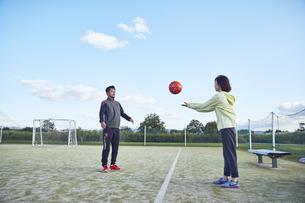 選手にボールを投げ渡すマネージャーの写真素材 [FYI04816597]