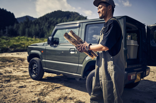 車から薪を取り出す男性の写真素材 [FYI04816711]