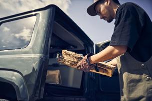 車から薪を取り出す男性の写真素材 [FYI04816712]
