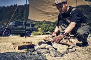 焚き火台に薪を置く男性の写真素材 [FYI04816714]