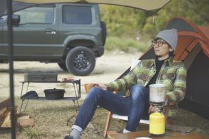 テントの前に座ってくつろぐ男性の写真素材 [FYI04816721]