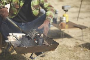 焚き火台の上で火を起こす男性の手元の写真素材 [FYI04816723]