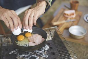 屋外でフライパンに卵を落とす男性の手元の写真素材 [FYI04816728]