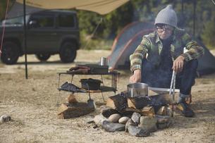 焚き火でお湯を沸かす男性の写真素材 [FYI04816734]