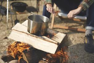 焚き火でお湯を沸かす男性の写真素材 [FYI04816735]
