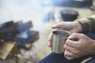 暖かい飲み物で温まる男性の手元の写真素材 [FYI04816737]