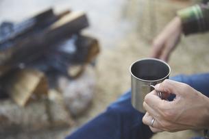キャンプでマグカップを持つ男性の手元の写真素材 [FYI04816738]
