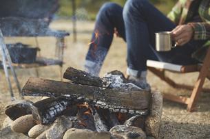 焚き火で暖をとる男性の写真素材 [FYI04816739]
