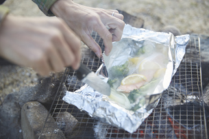 ホイル焼きのアルミホイルを開く男性の手元の写真素材 [FYI04816746]