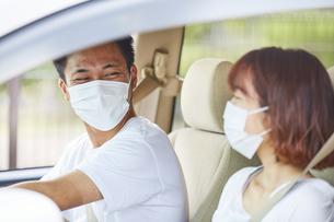 車の中でマスクをつけて会話する男女の写真素材 [FYI04816875]