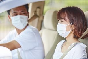 車の中でマスクをつけて会話する男女の写真素材 [FYI04816876]