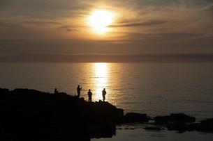 美しい海の夕暮れと釣り人のシルエットの写真素材 [FYI04817207]