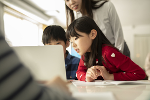 ICT教育 パソコンを見る小学生と教師の写真素材 [FYI04817706]