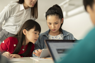 ICT教育 タブレットを見る小学生と教師の写真素材 [FYI04817707]