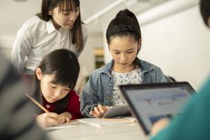 ICT教育 タブレットを見る小学生と教師の写真素材 [FYI04817708]
