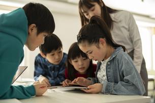ICT教育 タブレットを見る小学生と教師の写真素材 [FYI04817710]