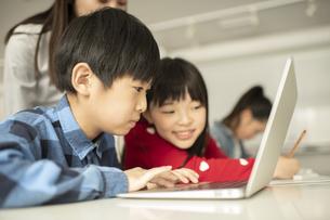 ICT教育 パソコンを見る小学生と教師の写真素材 [FYI04817769]