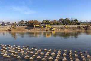 川岸で土砂を掘り起こす油圧ショベルの写真素材 [FYI04818685]